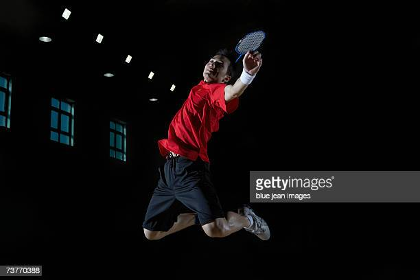 close-up of a young man as he leaps high in the air and prepares to smash a shuttlecock during a game of badminton. - badminton sport stock photos and pictures