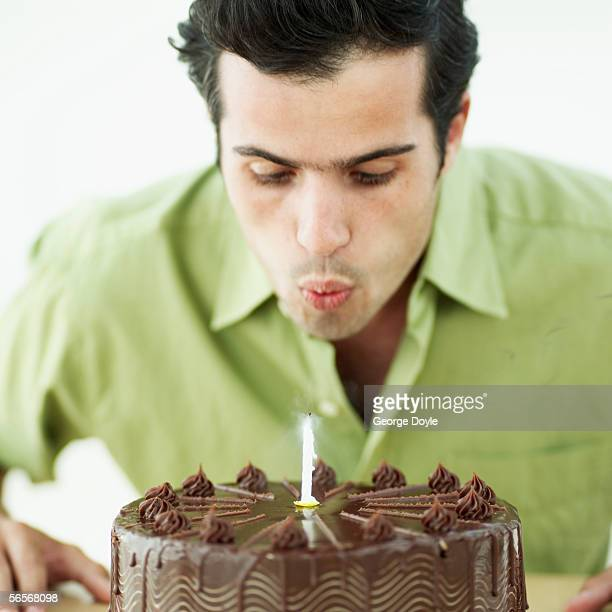 close-up of a young man blowing out a candle on a birthday cake
