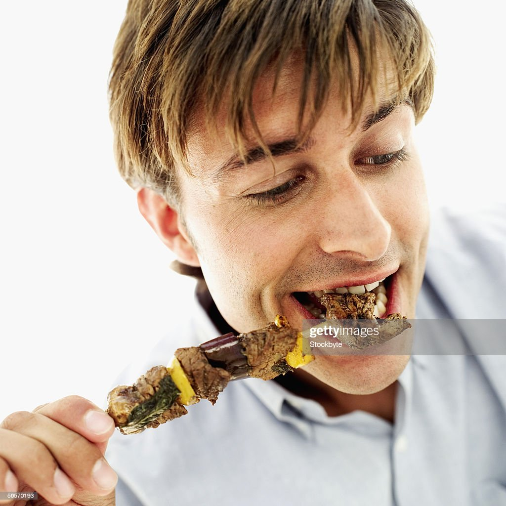 close-up of a young man eating a piece of meat from a skewer : Stock Photo