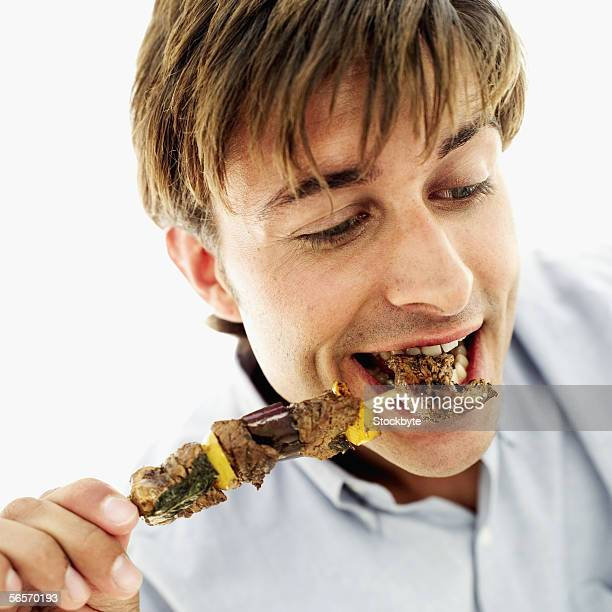 close-up of a young man eating a piece of meat from a skewer