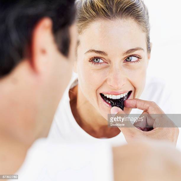 close-up of a young man feeding a prune to a young woman - dörrpflaume stock-fotos und bilder