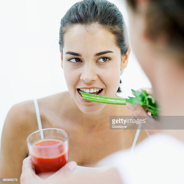 close-up of a young man feeding a young woman a celery stick