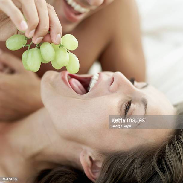 close-up of a young man feeding a young woman grapes