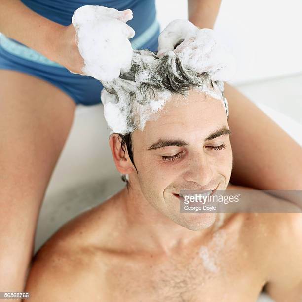 close-up of a young man getting his hair washed by a woman
