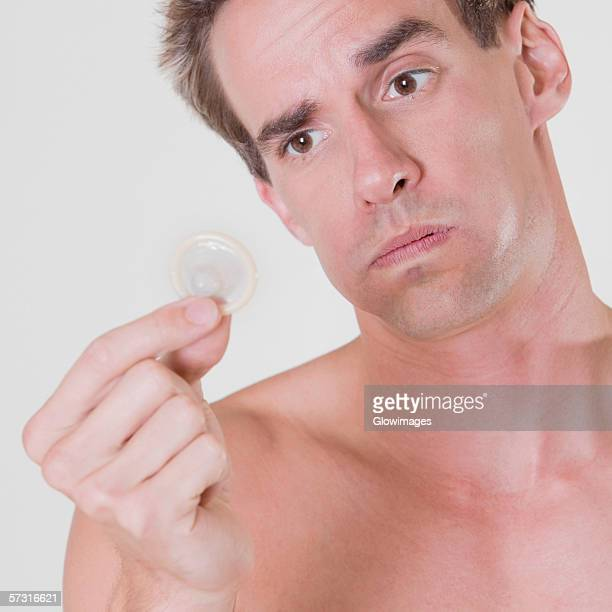 Close Up Of A Young Man Holding A Condom