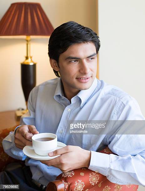 Close-up of a young man holding a cup of tea