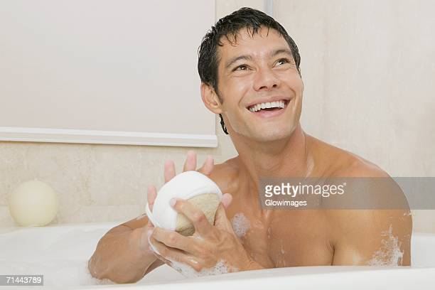 close-up of a young man holding a loofah in a bathtub - loofah stock photos and pictures