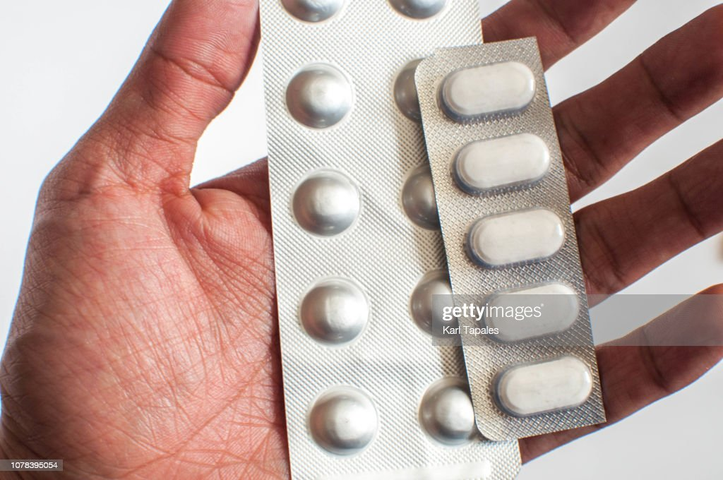 A close-up of a young man is holding a bunch of pills : Stock Photo