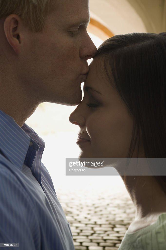 Close-up of a young man kissing a young woman : Foto de stock