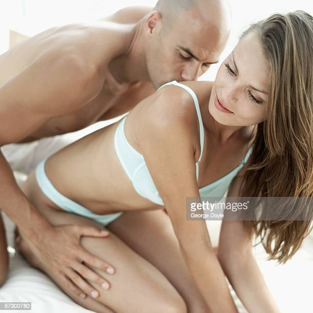 close-up of a young man kissing a young woman's back - leg kissing stock photos and pictures