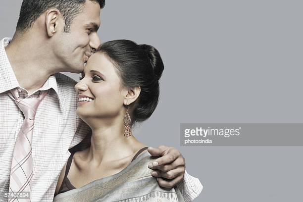 Close-up of a young man kissing a young woman's forehead