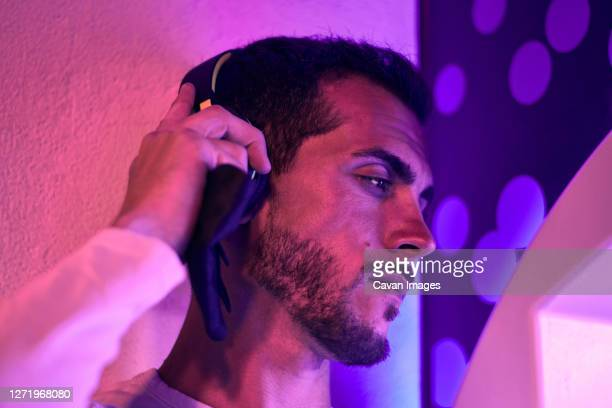 close-up of a young man listening music at night. color lights - mid adult stock pictures, royalty-free photos & images