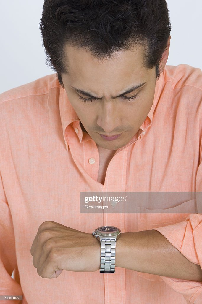 Close-up of a young man looking at his watch : Stock Photo
