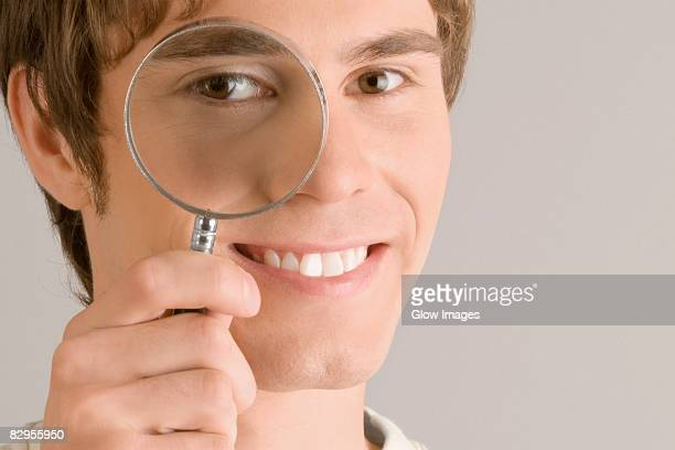 Close-up of a young man looking through a magnifying glass