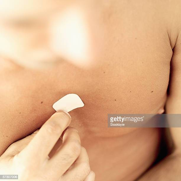 Close-up of a young man putting a nicotine patch on his chest