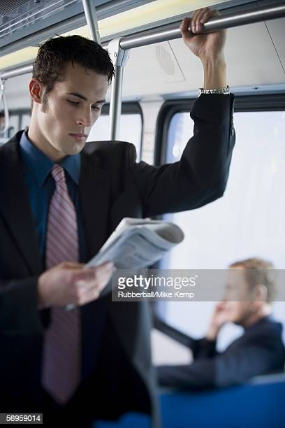 close-up of a young man reading a newspaper on a commuter train - 通勤電車 ストックフォトと画像