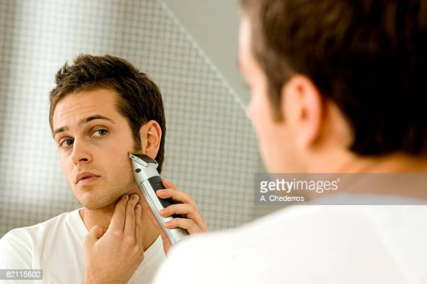 Close-up of a young man shaving with an electric razor