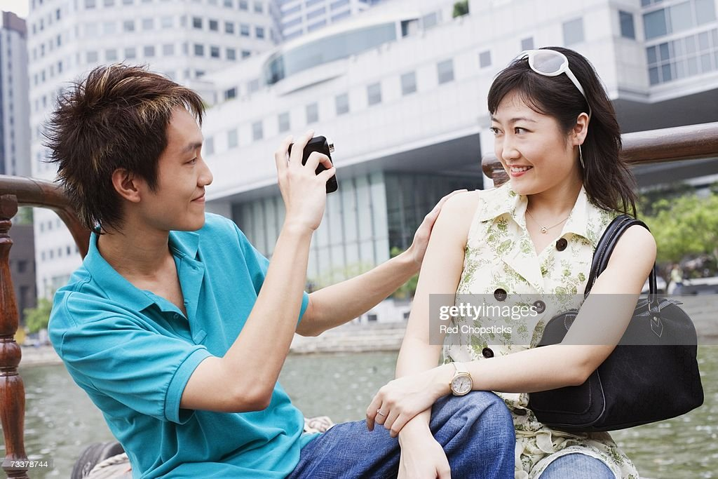 Close-up of a young man taking video of a young woman : Stock Photo