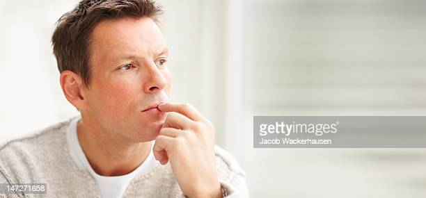 close-up of a young man thinking and looking away - kin in de hand stockfoto's en -beelden