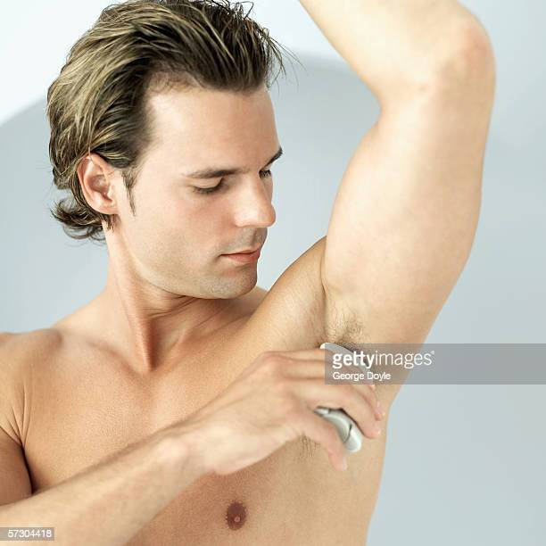 Close-up of a young man using a deodorant stick under his arm