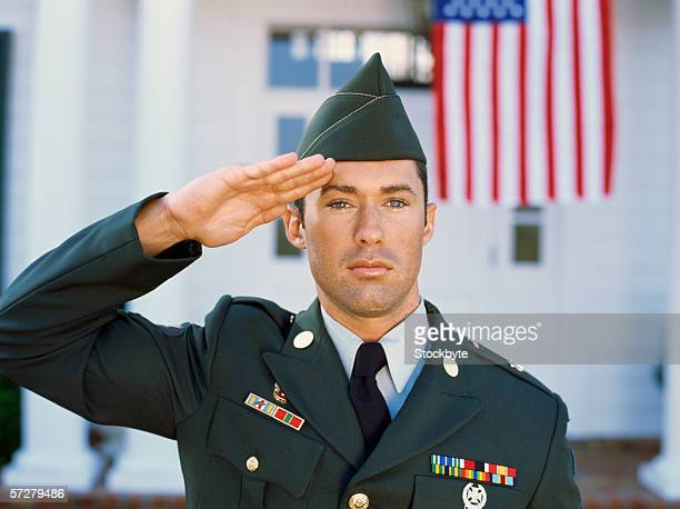 Close-up of a young man wearing a military uniform saluting
