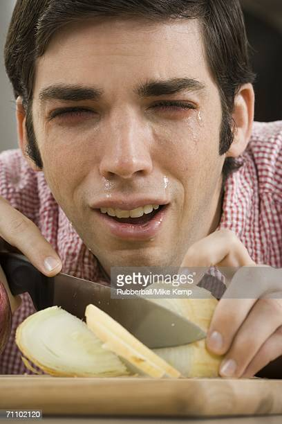 Close-up of a young man with tears in his eyes while cutting onions