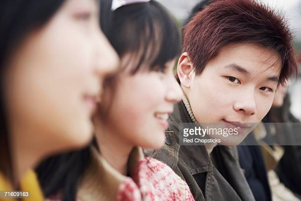 Close-up of a young man with two young women