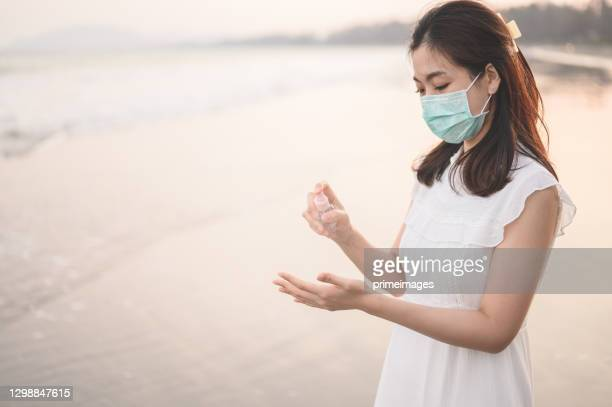 closeup of a young toursit asian on the beach disinfecting her hands - image title stock pictures, royalty-free photos & images