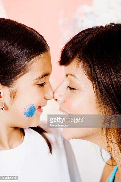 Close-up of a young woman and her daughter rubbing noses