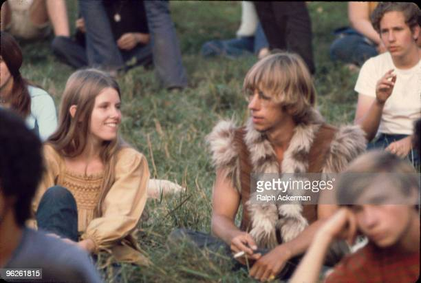 Closeup of a young woman and man the later dressed in a furry vest as they sit on the grass near the 'Free Stage' at the Woodstock Music and Arts...