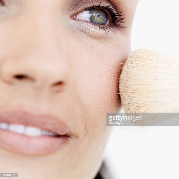 close-up of a young woman applying blush with a brush