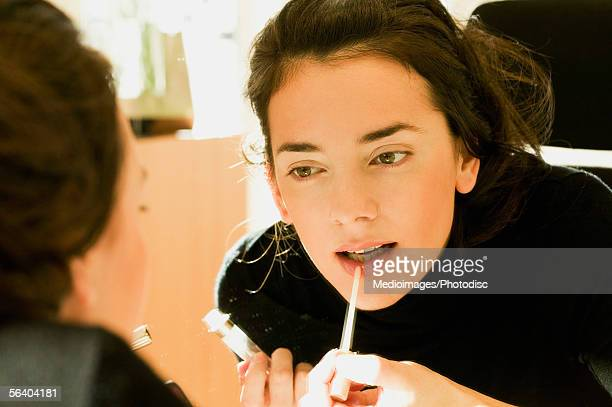 Close-up of a young woman applying lip liner