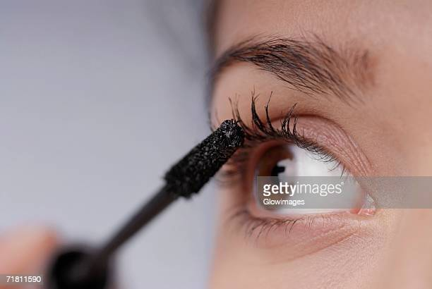 Close-up of a young woman applying mascara