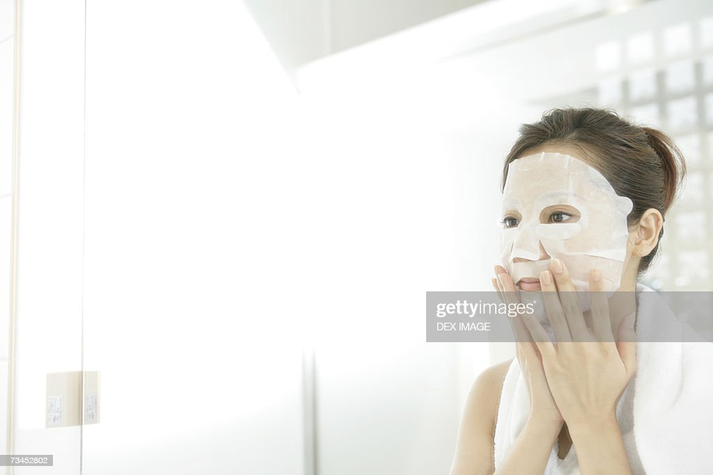 Close-up of a young woman applying paper facial mask : Stock Photo