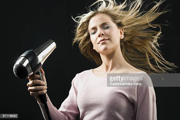 Close-up of a young woman blow drying her hair