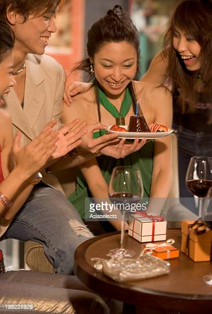 Close-up of a young woman blowing out a candle on a cake with her friends around her