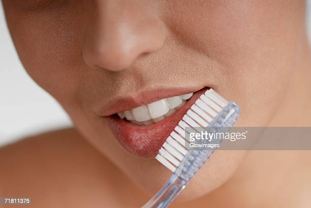 Close-up of a young woman brushing her teeth