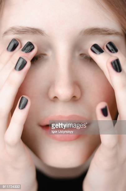 close-up of a young woman covering her eyes with her fingers - black nail polish stock photos and pictures