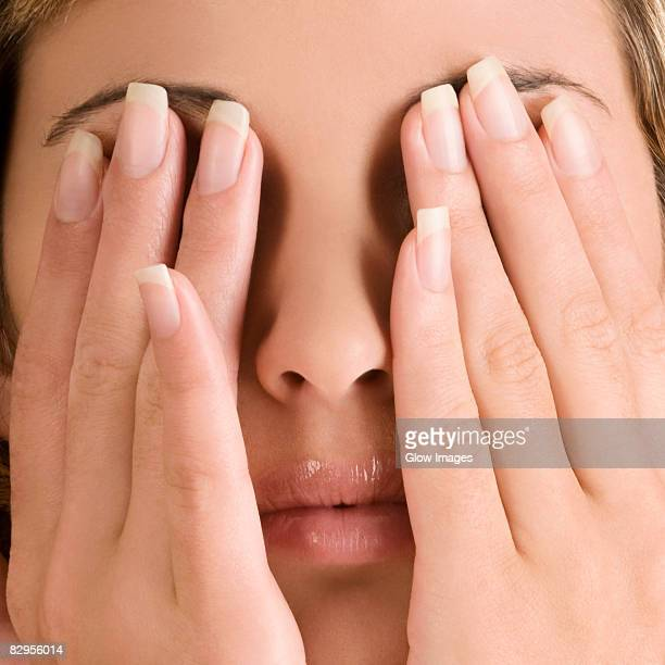 Close-up of a young woman covering her eyes with her hands