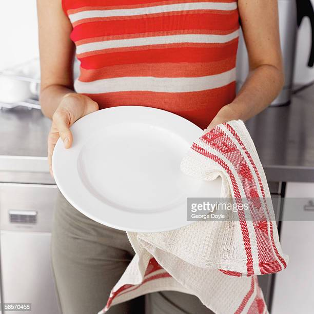 close-up of a young woman drying dishes with a rag