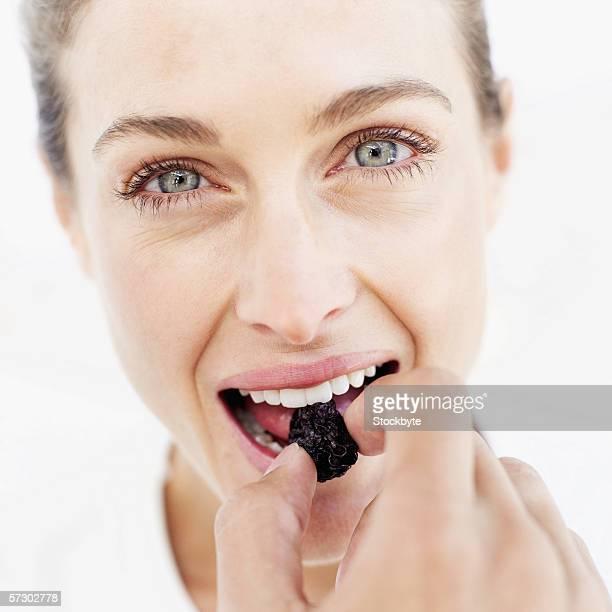 close-up of a young woman eating a prune - dörrpflaume stock-fotos und bilder