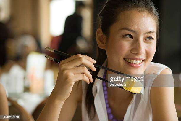 Close-up of a young woman eating dim sum in a restaurant and smiling