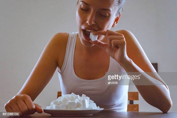 Close-up of a young woman eating sugar cubes from the plate before her