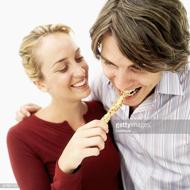 Close-up of a young woman feeding a breadstick to a young man
