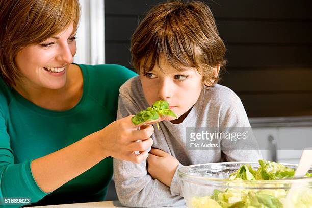 Close-up of a young woman feeding basil to her son