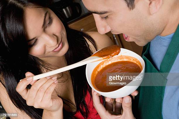 Close-up of a young woman feeding tomato soup to a mid adult man in the kitchen