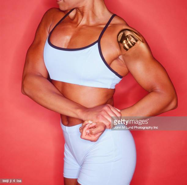 close-up of a young woman flexing her muscles - female bodybuilder stock photos and pictures
