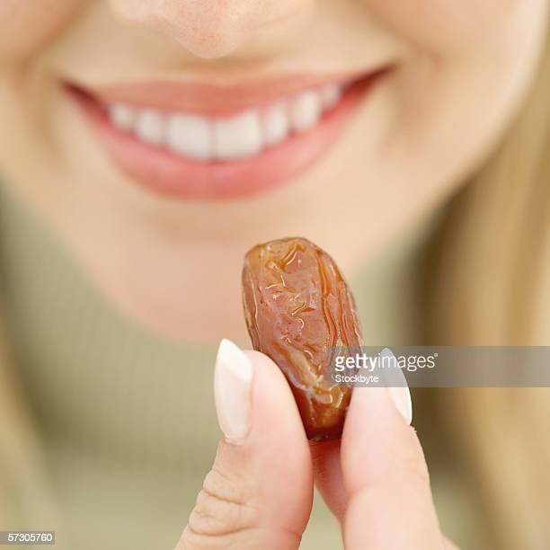 close-up of a young woman holding a prune - dörrpflaume stock-fotos und bilder