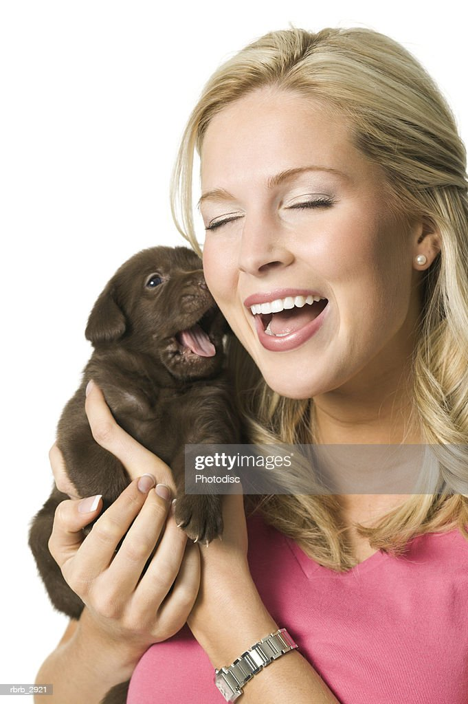Close-up of a young woman holding a puppy : Foto de stock