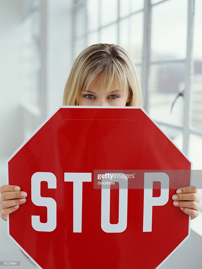 Close-up of a young woman holding a stop sign : Stock Photo